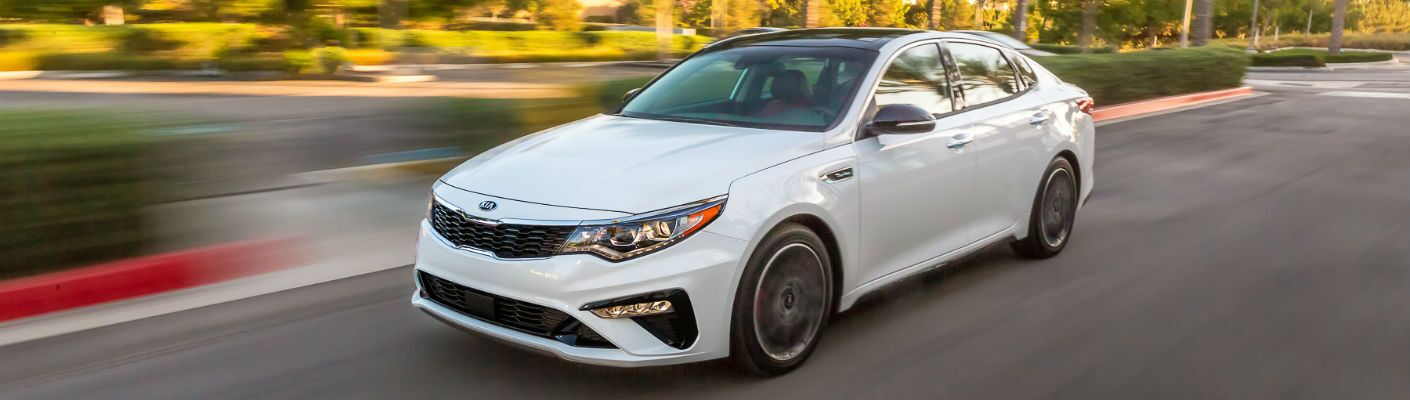 A front left quarter photo of the 2020 Kia Optima in motion on the road.
