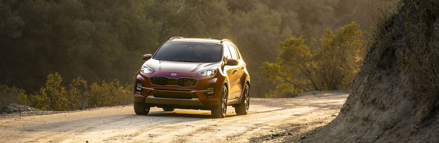 A head-on photo of the 2020 Kia Sportage coming around a corner on a dirt road.