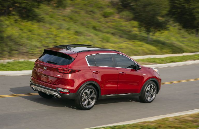 A right profile photo of the 2020 Kia Sportage in motion on the road.