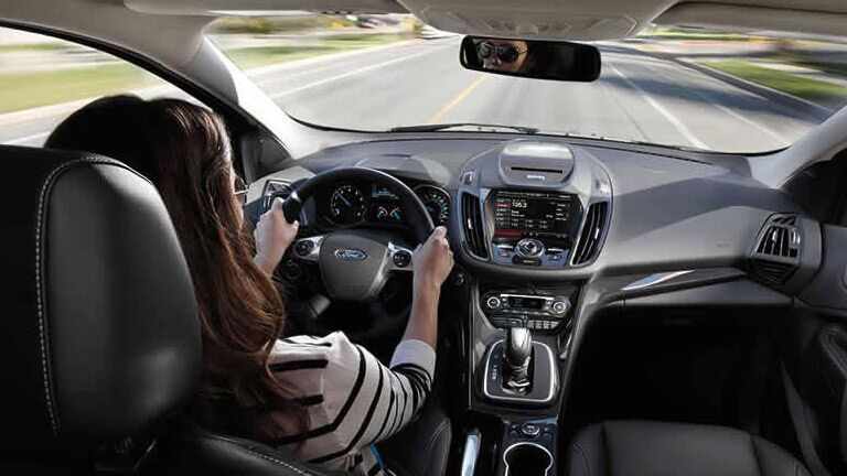 Interior view of a woman driving a 2015 Ford Escape down a highway.