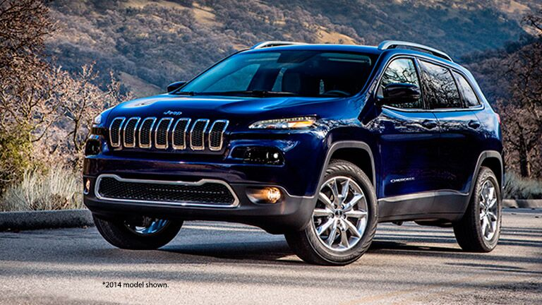 Blue 2014 Jeep Cherokee parked on a road in the wilderness.