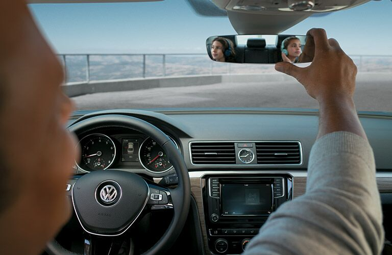 Man checking rearview mirror in 2016 Volkswagen Passat