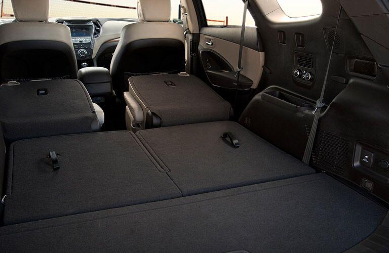 Interior rear cargo area with all seats folded down inside a 2017 Hyundai Santa Fe.
