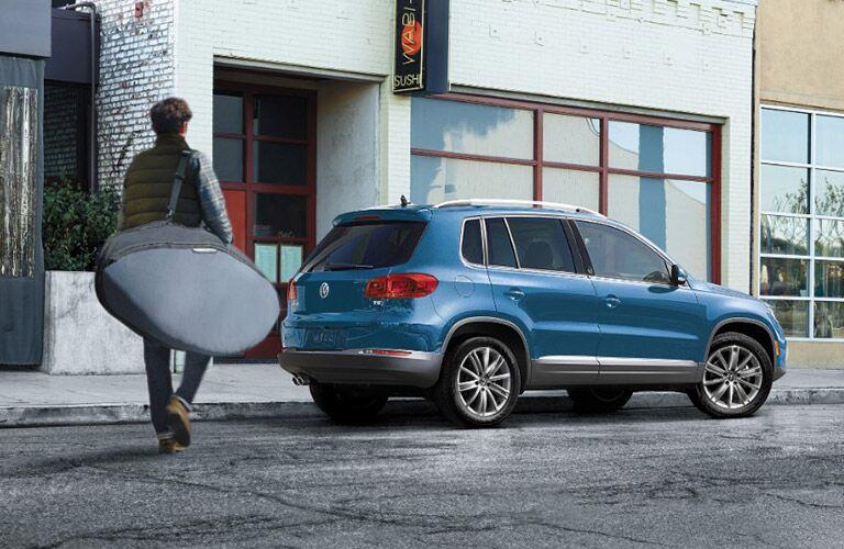 man with surfboard approaching blue 2017 VW Tiguan