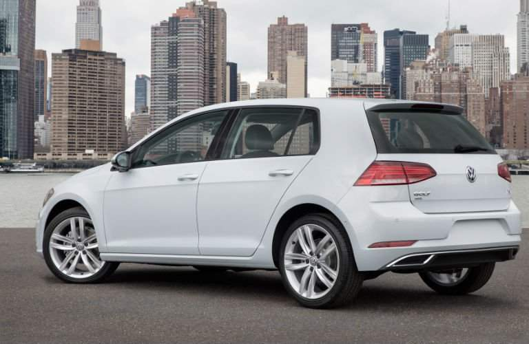 Rear profile of the 2018 Volkswagen Golf parked overlooking a body of water and a cityscape