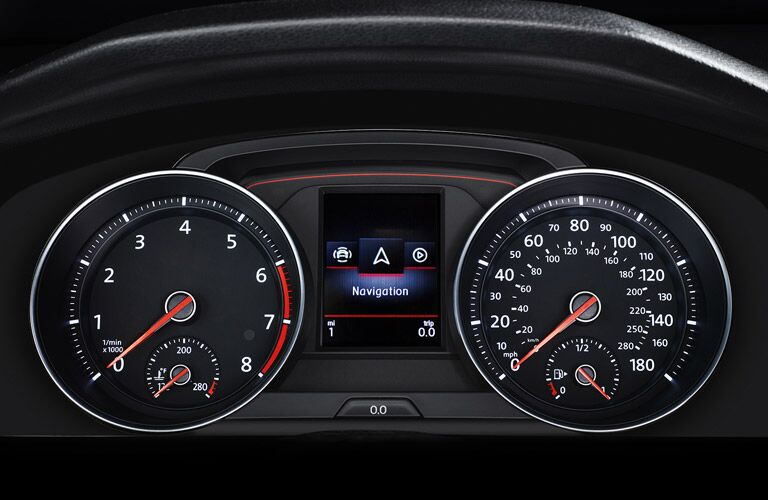 A speedometer and RPM indicator sit on either side of a digital navigation screen on the Golf GTI dashboard.