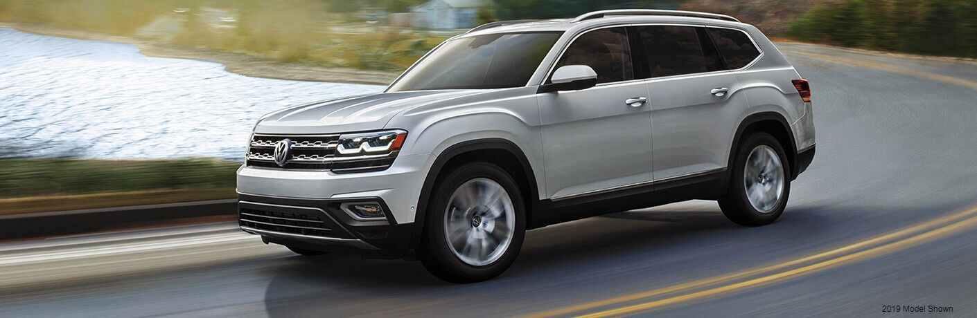 Silver Volkswagen Atlas zips around a highway curve.