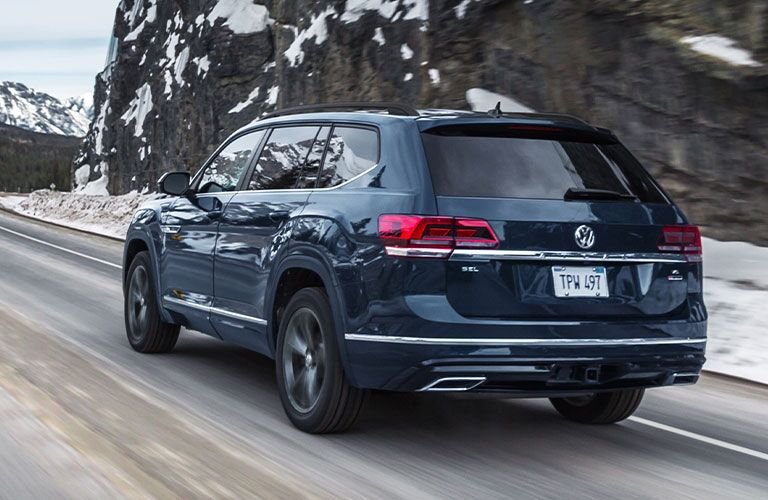 Rear view of a 2020 Volkswagen Atlas driving through a snowy clime