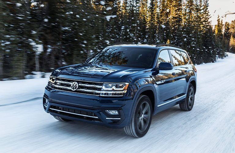 Front/side view of a blue 2020 Volkswagen Atlas rolling through a snowy clime