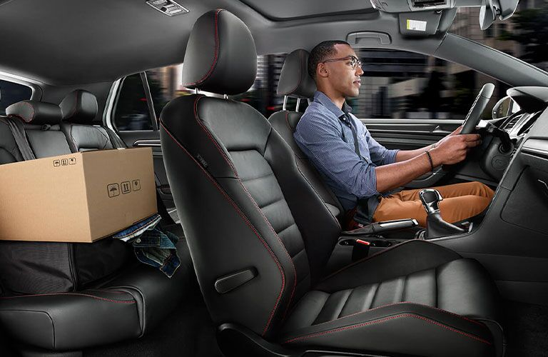 A man chauffeurs a cardboard box inside a 2020 VW Golf GTI