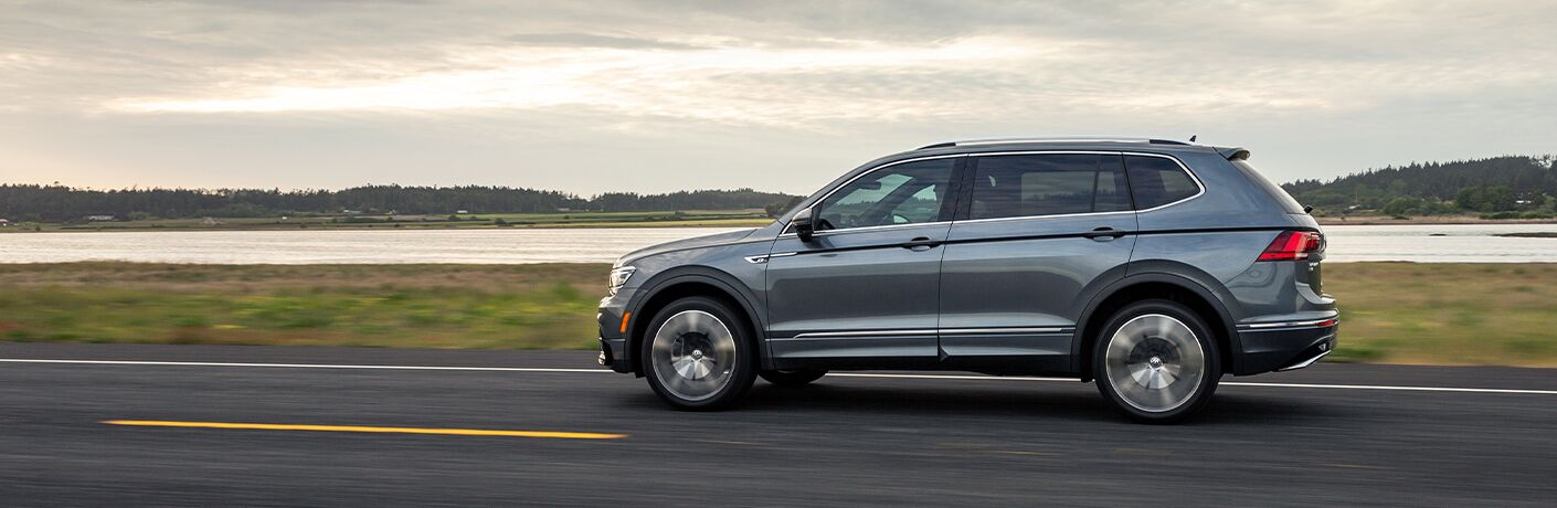 Silver 2020 Volkswagen Tiguan zips along a highway, enjoying its warranty coverage