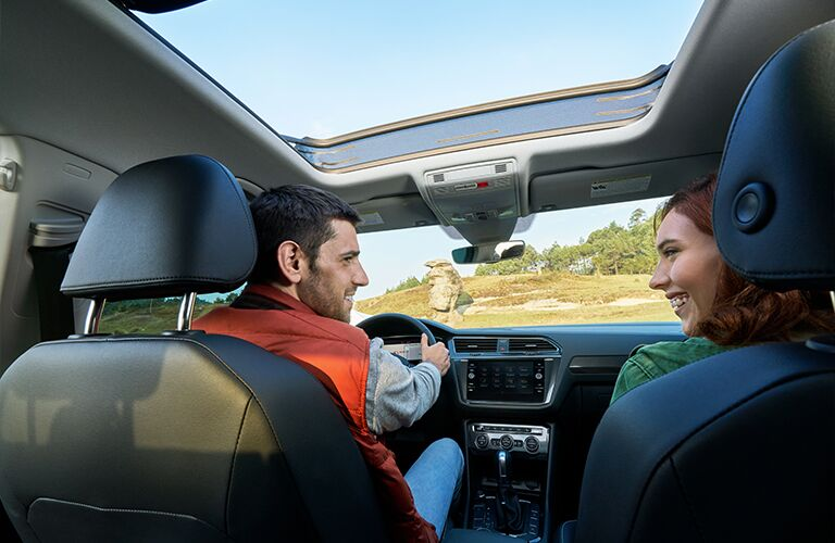 Two people enjoy themselves in the cabin of a 2020 Tiguan.