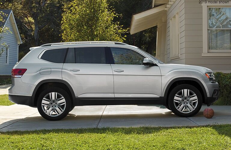 Side view of a silver Volkswagen Atlas almost touching a basketball.