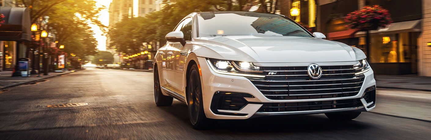 Head-on view of a white 2020 Volkswagen Arteon driving up a lamplit city street at dusk.