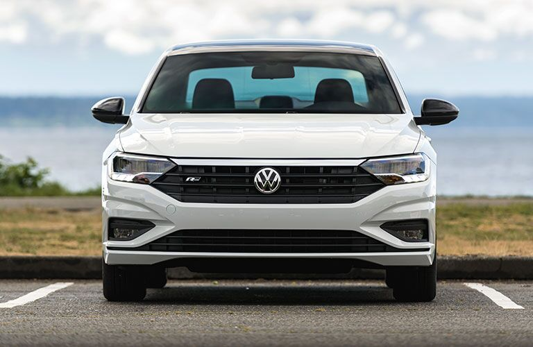 head-on view of a white 2020 Volkswagen Jetta parked by the seashore.