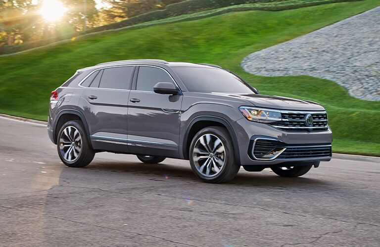 2021 Volkswagen Atlas Cross Sport drives by a green hill
