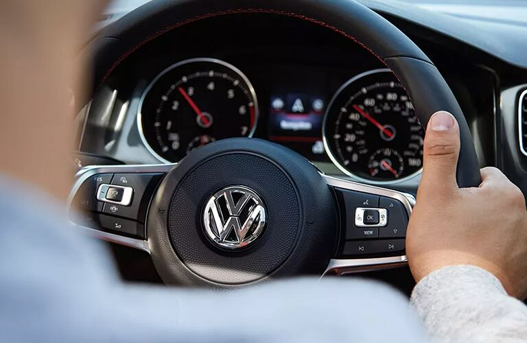 Man grips steering wheel of a 2021 Volkswagen Golf GTI