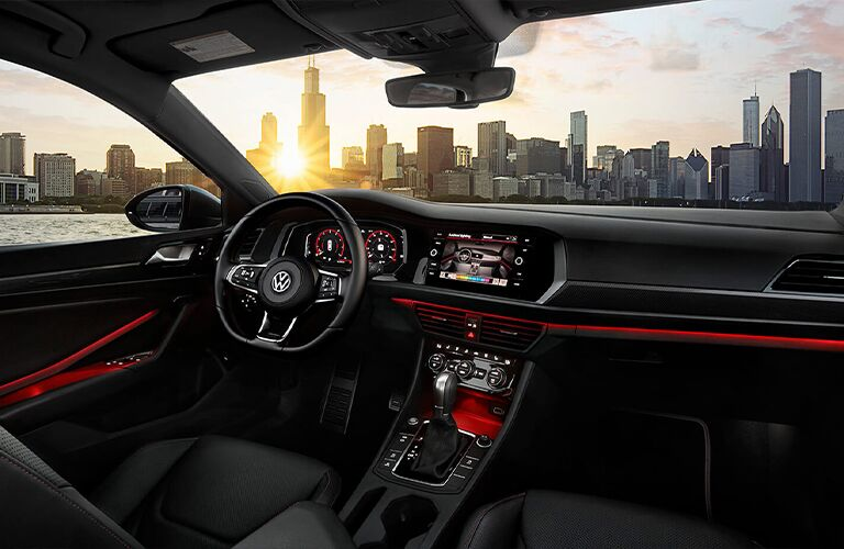 City skyline viewed through the windshield and cockpit of a2021 Volkswagen Jetta GLI