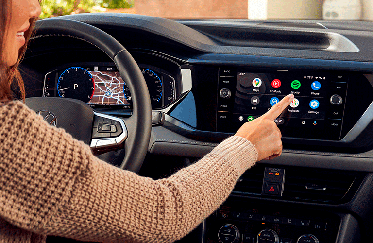 """Woman extends finger to press the """"Spotify"""" icon on the infotainment screen of the 2022 Volkswagen Taos, but stops herself"""