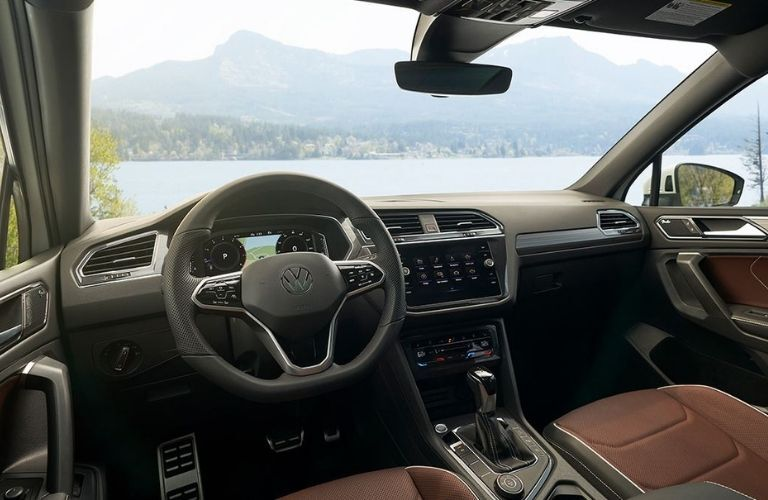 The cockpit of the 2022 Volkswagen Tiguan parked in front of a water body.