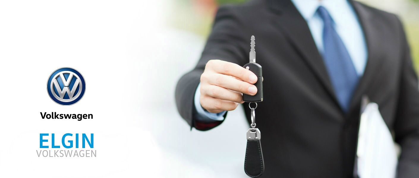 auto salesperson holding out car key