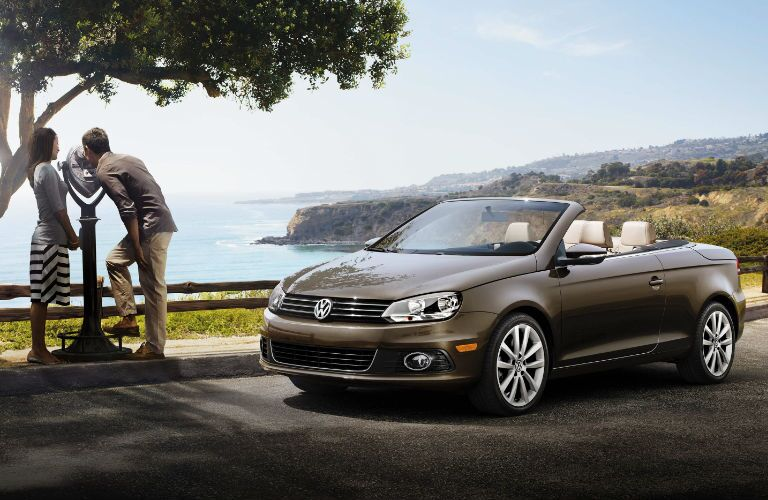 A couple sight-sees with the 2016 VW Eos behind them.