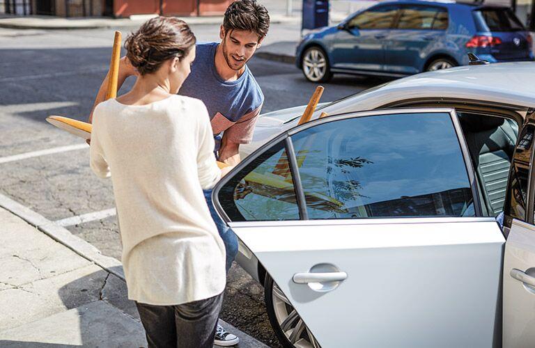 couple loading the rear passenger door of VW Jetta