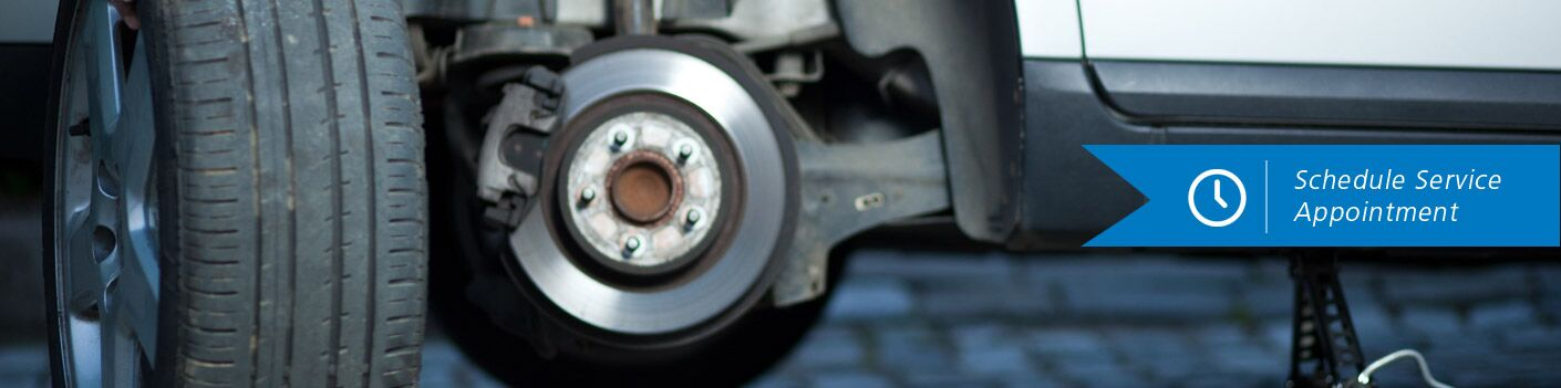 Close up of the brakes and wheel on a car with the text Schedule Service Appointment on the right side