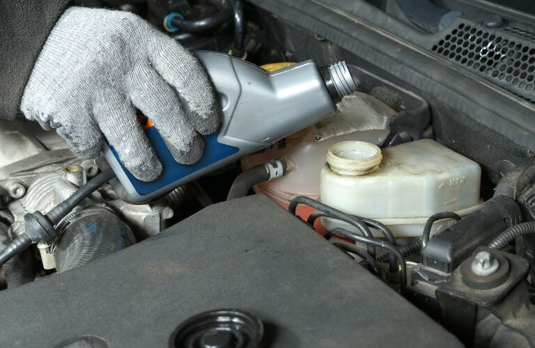 brake fluid being poured into a reservoir