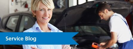 Woman smiling as a technician works on a car in the background with the text Service Blog in bottom left corner