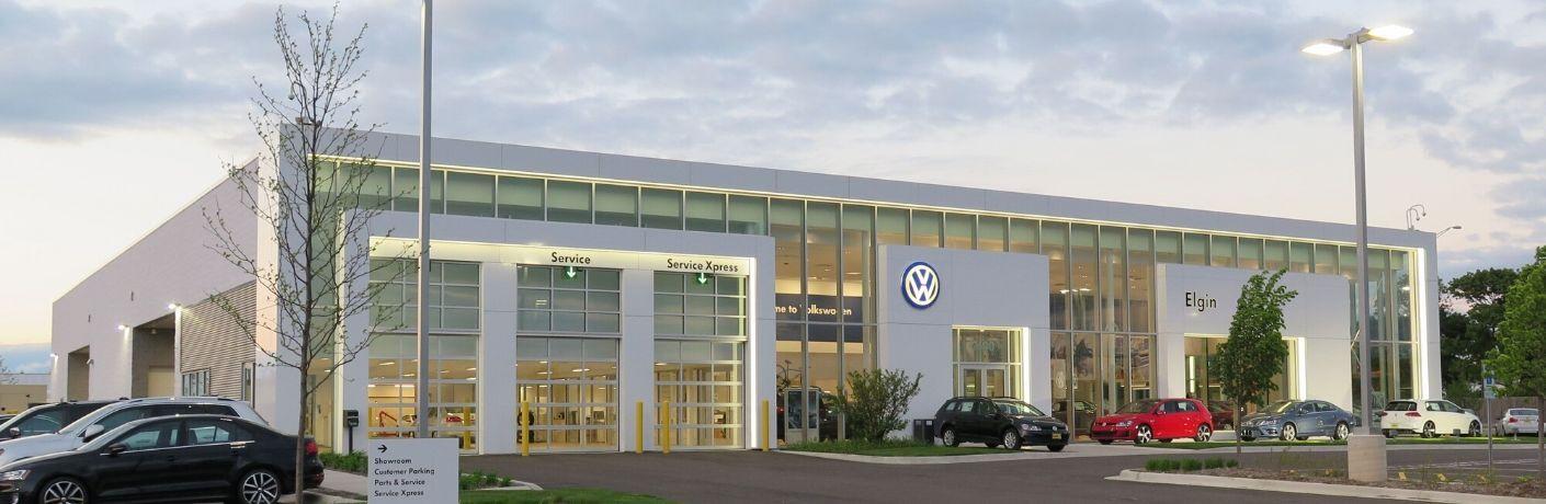 Exterior image of Elgin Volkswagen dealership under a setting sun.