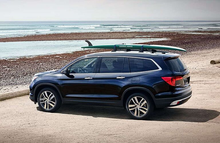 Exterior view of a blue 2018 Honda Pilot parked at a beach with a surfboard on the roof rack