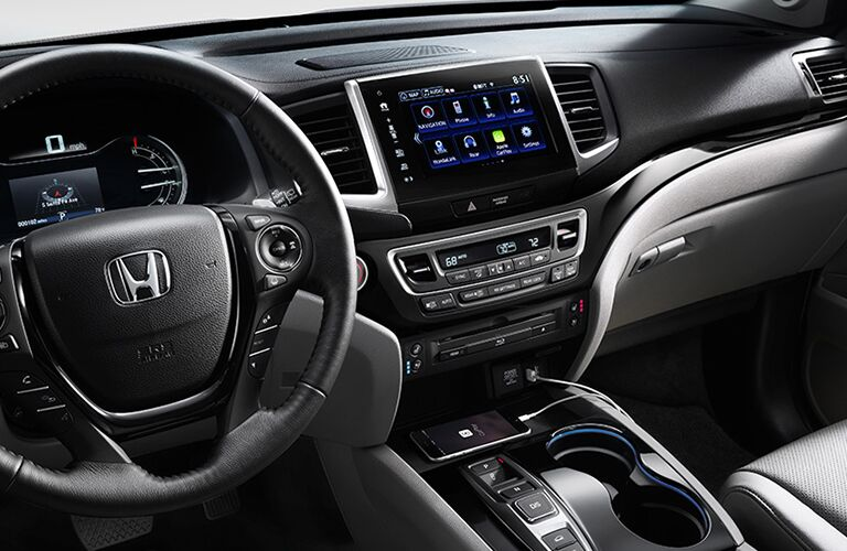 Interior view of a black steering wheel and touchscreen of a 2018 Honda Pilot