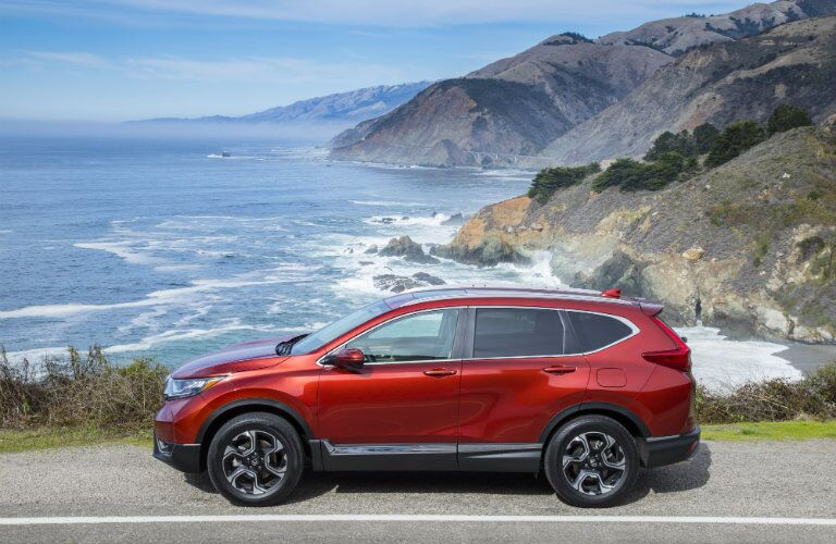 Exterior view of the driver's side of a red 2018 Honda CR-V parked on an ocean-side street