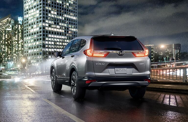 Exterior view of the rear of a grey 2019 Honda CR-V driving down a city street