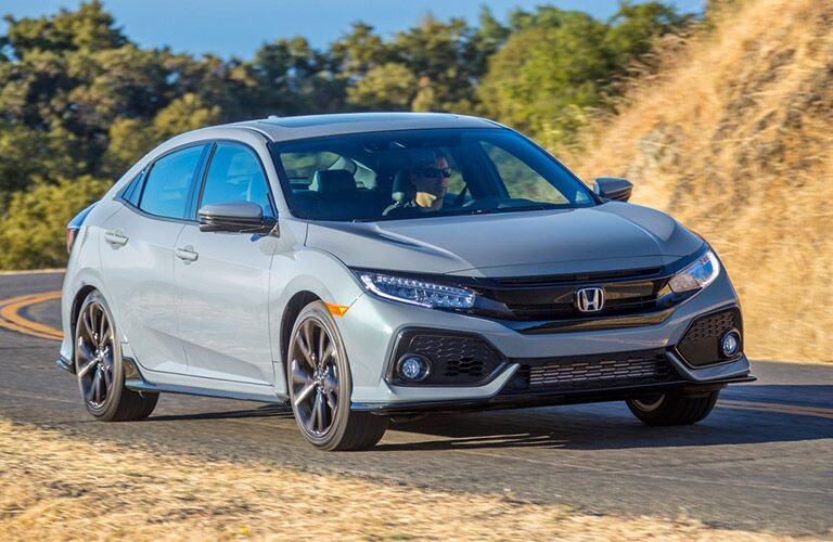 Exterior view of the front of a gray 2019 Honda Civic Hatchback driving down a country highway