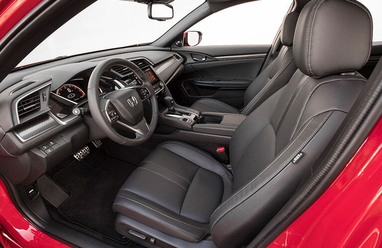 Interior view of the front seats and steering wheel inside a red 2019 Honda Civic Hatchback