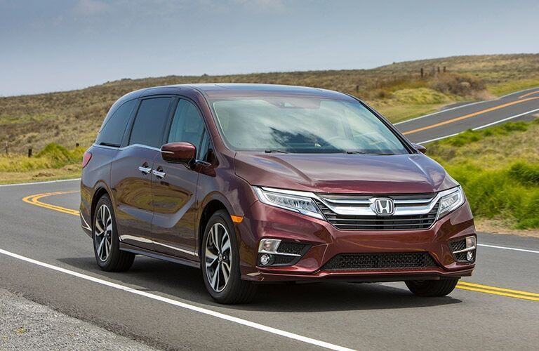 Exterior view of the front of a red 2019 Honda Odyssey driving down a two-lane road