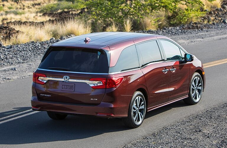 Exterior view of the rear of a red 2019 Honda Odyssey driving down a two-lane road