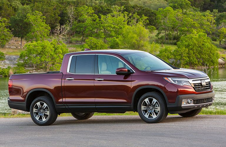 Exterior view of a dark red 2018 Honda Ridgeline parked outside on pavement with trees in the background