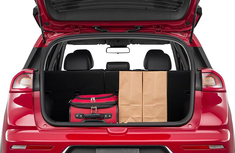2018 Kia Niro red paint with trunk open to show cargo space against white background