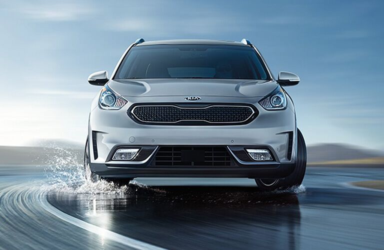 2018 Kia Niro gray driving outside on wet road with hills in the background