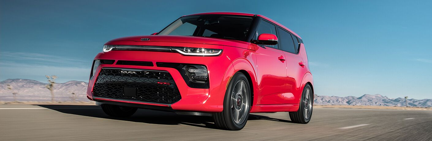 front quarter exterior photo of red 2020 Kia Soul driving on highway