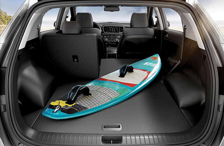 rear cargo area of a 2021 Kia Sportage with a surf board in it