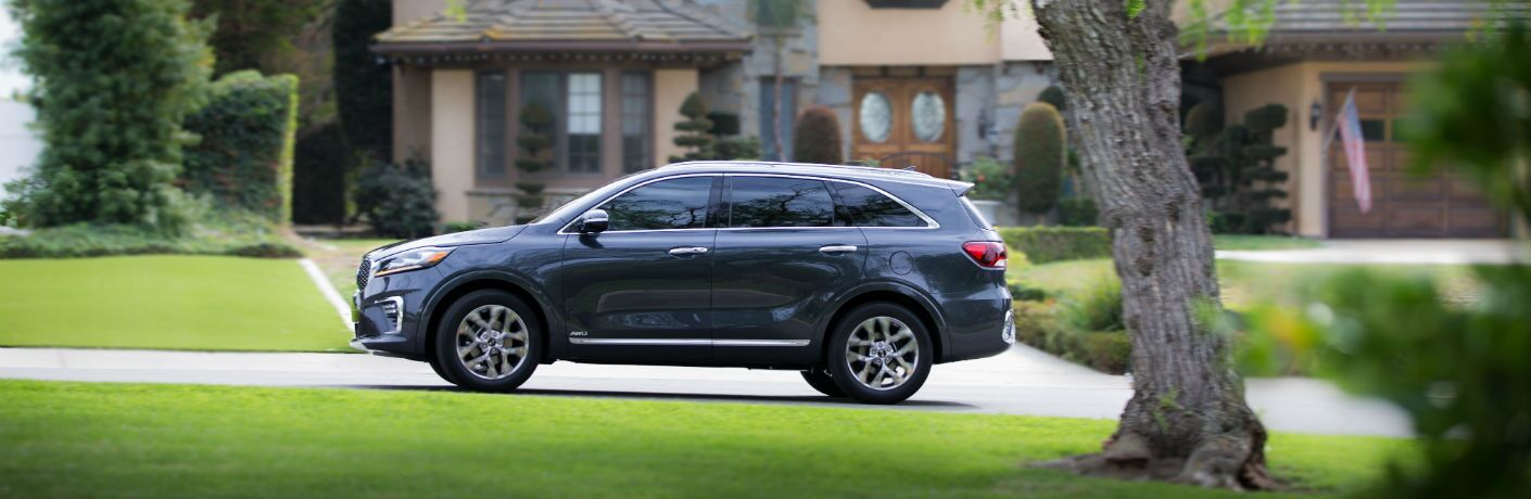 A left profile photo of the 2019 Kia Sorento parked in front of a home.