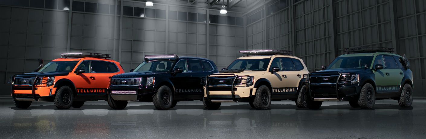 A photo of four Kia Telluride SEMA concept vehicles lined up side-by-side in a hangar.
