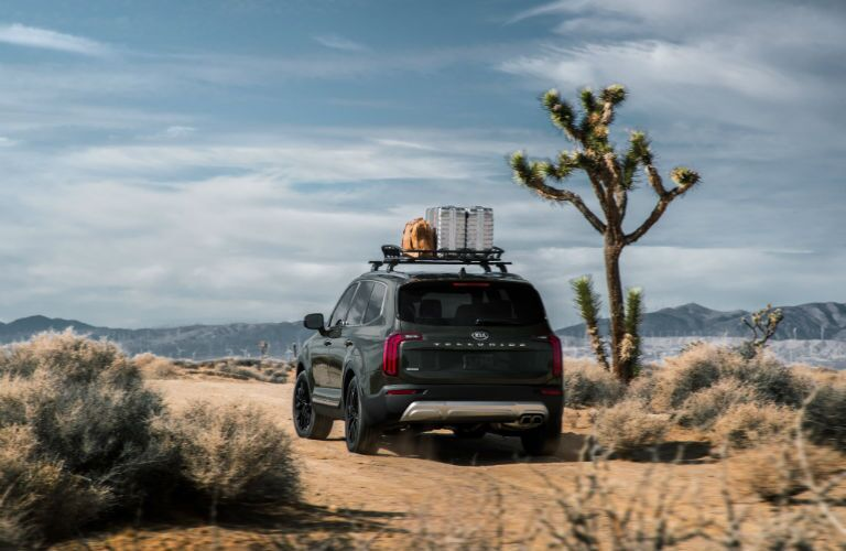 A rear photo of the 2020 Kia Telluride outfitted with a roof rack and parked in the desert.