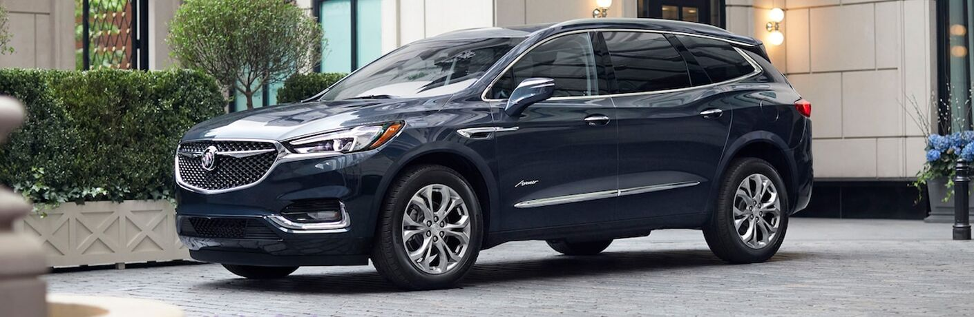 2019 Buick Enclave exterior shot with dark blue paint color parked on a tiled plaza near gardens