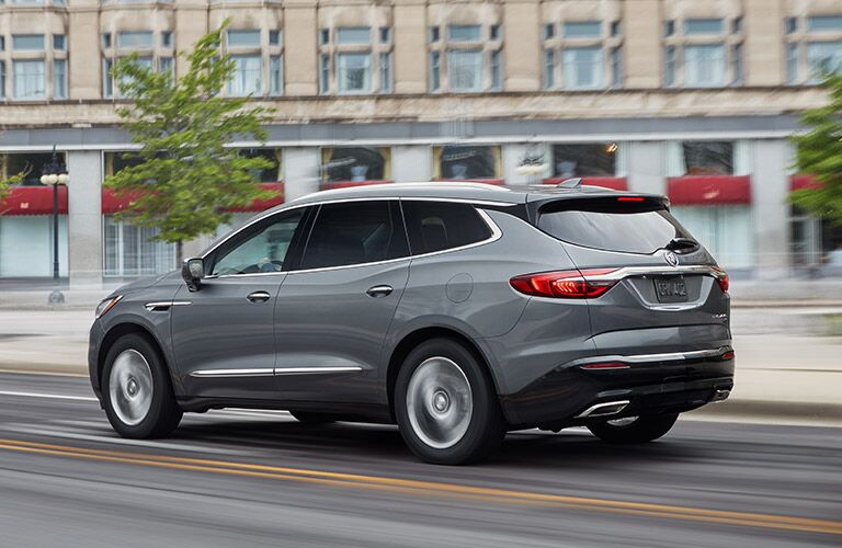 2019 Buick Enclave exterior side shot with gray metallic paint color driving through a city during the daytime