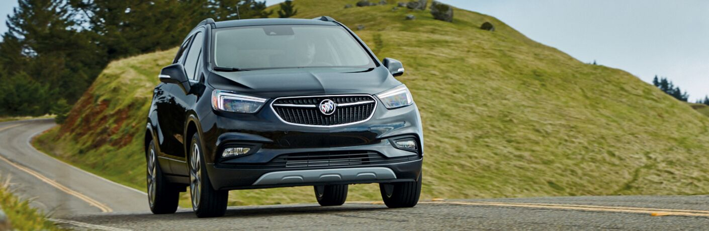 2019 Buick Encore exterior front shot driving through the country on a road between green hills and a cloudy sky